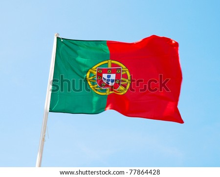 Flag of Portugal waving, against blue sky - stock photo