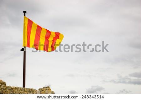 Flag of Provence waving over castle ruins in Les Baux-de-Provence village, France. - stock photo