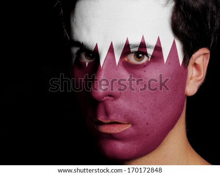 Flag of Qatar Painted on a Face of a Young Man - stock photo