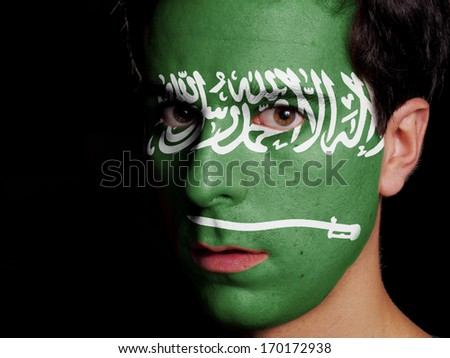 Flag of Saudi Arabia Painted on a Face of a Young Man - stock photo