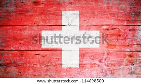 Flag of Switzerland painted on grungy wood plank background - stock photo