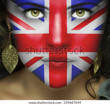 Flag of the United Kingdom on the woman's face with green eyes - stock photo