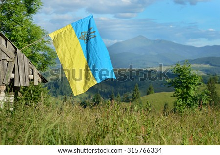Flag of Ukraine on an old house on a background of the Carpathian Mountains - stock photo