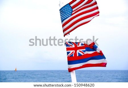 Flag of United States of America and State of Hawaii flying on a ship mast on the open Pacific Ocean - stock photo