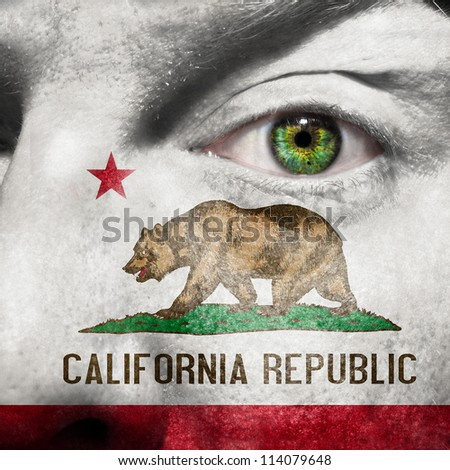 Flag painted on face with green eye to show California support - stock photo