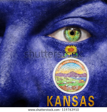 Flag painted on face with green eye to show Kansas support - stock photo