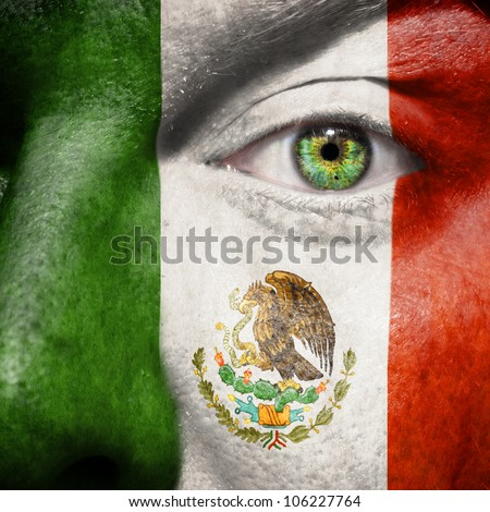 Flag painted on face with green eye to show mexico support - stock photo