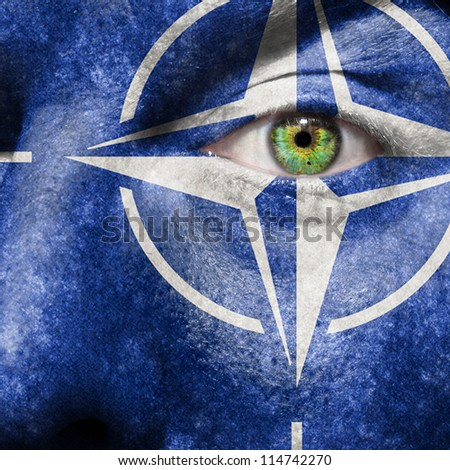 Flag painted on face with green eye to show NATO support - stock photo