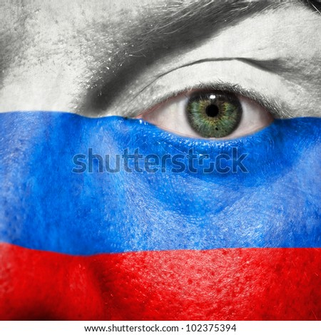 Flag painted on face with green eye to show Russia support in sport matches - stock photo