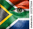 Flag painted on face with green eye to show South Africa support in sport matches - stock photo