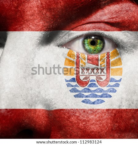 Flag painted on face with green eye to show Tahiti or French Polynesia support