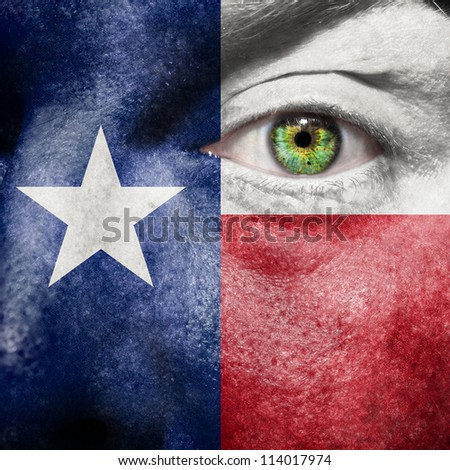 Flag painted on face with green eye to show Texas support - stock photo