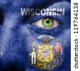 Flag painted on face with green eye to show Wisconsin support - stock photo