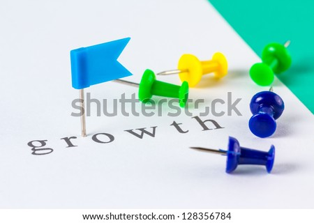 Flag push pin on paper at growth word - stock photo