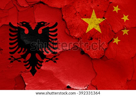 flags of Albania and China painted on cracked wall