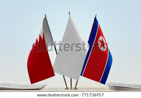 Flags of Bahrain and North Korea with a white flag in the middle