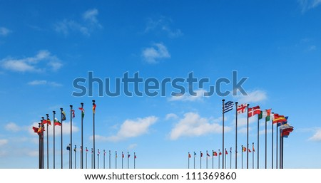 Flags of different countries on a flagpole against a blue sky - stock photo