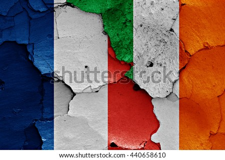 flags of France and Ireland painted on cracked wall - stock photo