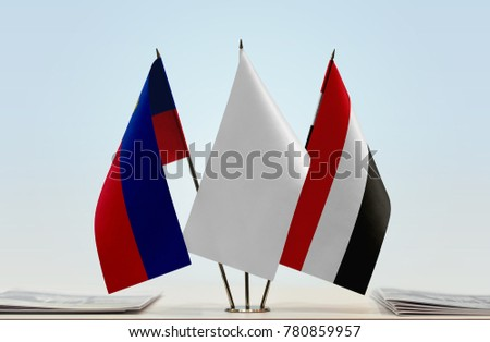 Flags of Liechtenstein and Yemen with a white flag in the middle
