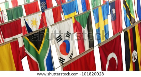 Flags of many countries hang vertically, representing a host of ethnic diversity from many cultures. - stock photo
