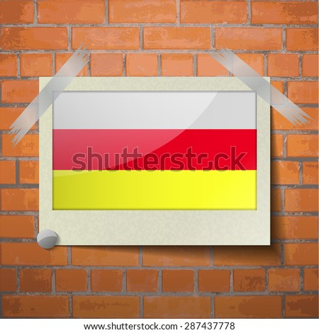 Flags of North Ossetia scotch taped to a red brick wall.  Rasterized version - stock photo