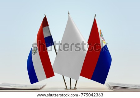 Flags of Paraguay and Sint Maarten with a white flag in the middle