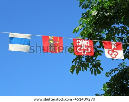 Flags of Swiss cantons hanging on rope for the Swiss National Day - stock photo
