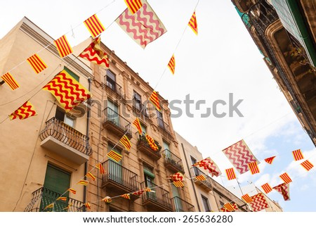 Flags of Tarragona city and Catalonia hanging over street, holiday street decoration - stock photo