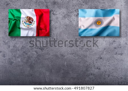 Flags of the mexico and argentina on concrete background.