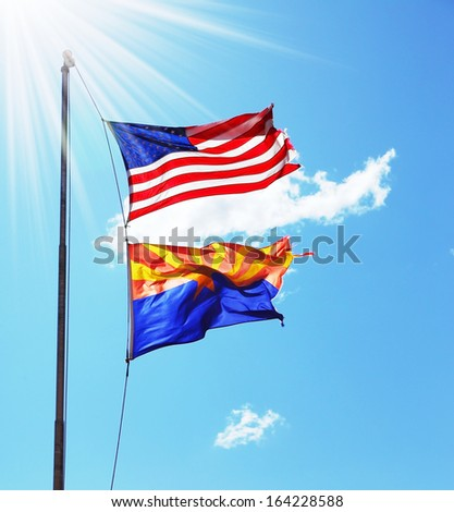 Flags of the United States and the Navajo Reservation are flying against the shining sun