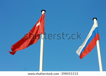 Flags of Turkey and Russia on the blue sky background