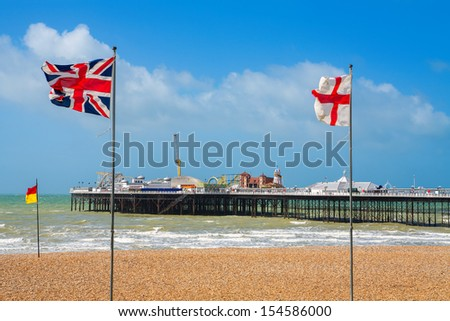 Flags on a beach and pier at Brighton. East Sussex, England - stock photo