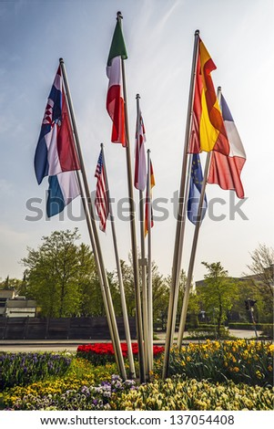 Flags on flagpoles of different countries of the world - stock photo