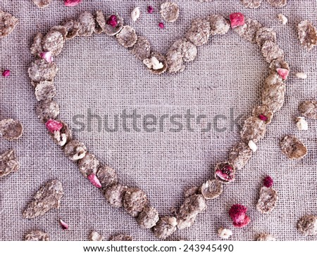 Flakes of different cereals with dry strawberry in heart-shape on burlap background - stock photo