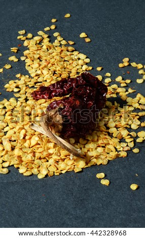 Flakes of red hot chili peppers and one dried chili pepper over stone background - stock photo