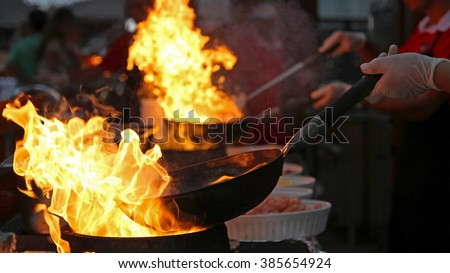 Flambe Chef Cooking in Outdoor Kitchen. Professional chef in a commercial kitchen cooking flambe style. Chef Flambe Cooking. - stock photo