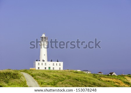 Flamborough, Yorkshire, UK.  View of the modern lighthouse on top of the chalk cliffs at Flamborough Head at dawn on a summer day.