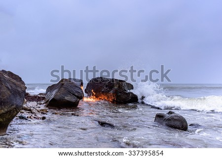 Flame between of the boulders on the seashore - stock photo