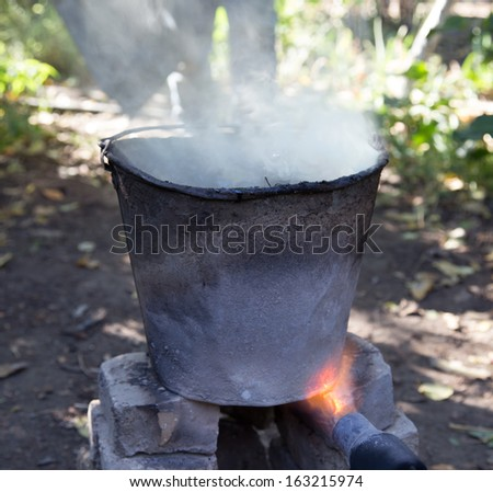 flame from a gas burner heats the bucket - stock photo