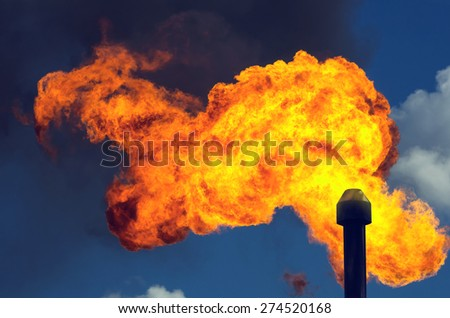 Flame in the sky from burning of associated gas at oil production - stock photo