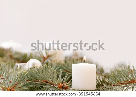 flame of the candle and fir branch on a white background - stock photo