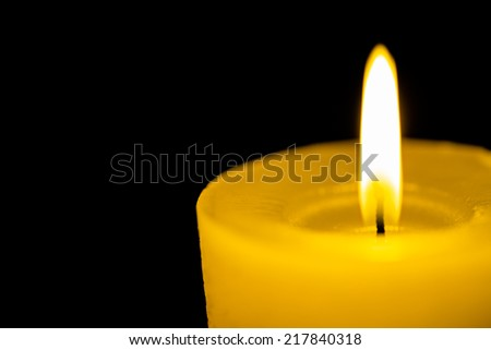 Flame on yellow candle in black dark  - stock photo
