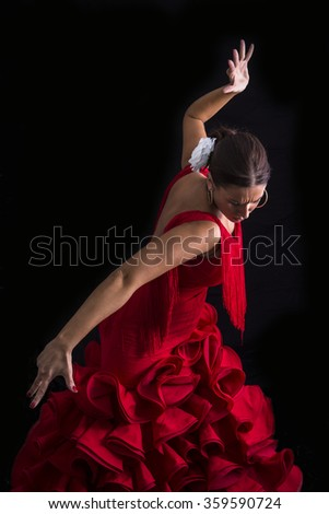 Flamenco dancer dressed in red with an expression of feeling passionate in black background - stock photo