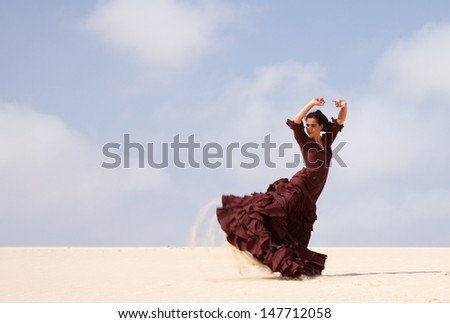 Flamenco dancer in the long dress in the dunes - stock photo