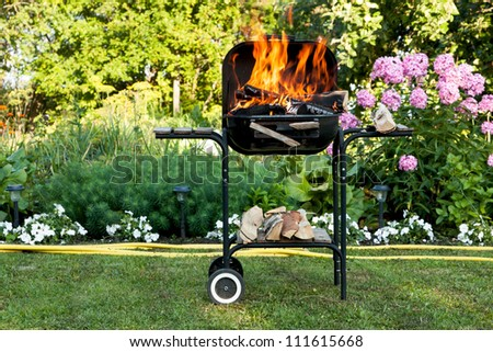Flames burning in a barbecue standing in a pretty garden as the coals are prepared for grilling an array of meat for a lunchtime cookout - stock photo