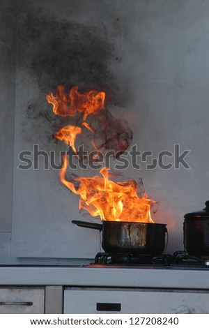 flames from burning oil on a kitchen stove - stock photo
