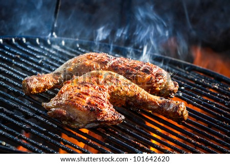Flames frying chicken on the grill