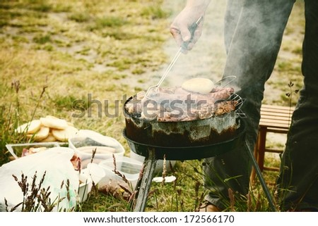 Flames grilling a steak on the BBQ bonfire, campfire summer - stock photo