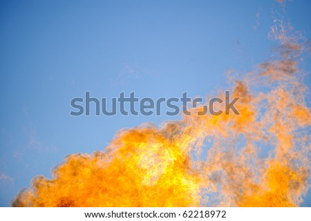Flames reach into the sky from a propane fire. - stock photo