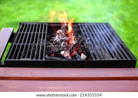 Flaming charcoal in BBQ appliance. Lawn in the background. - stock photo